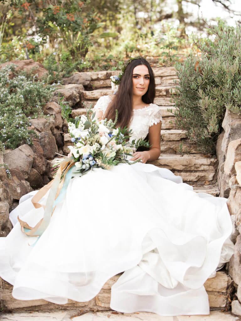 Bride sitting on a rock steps