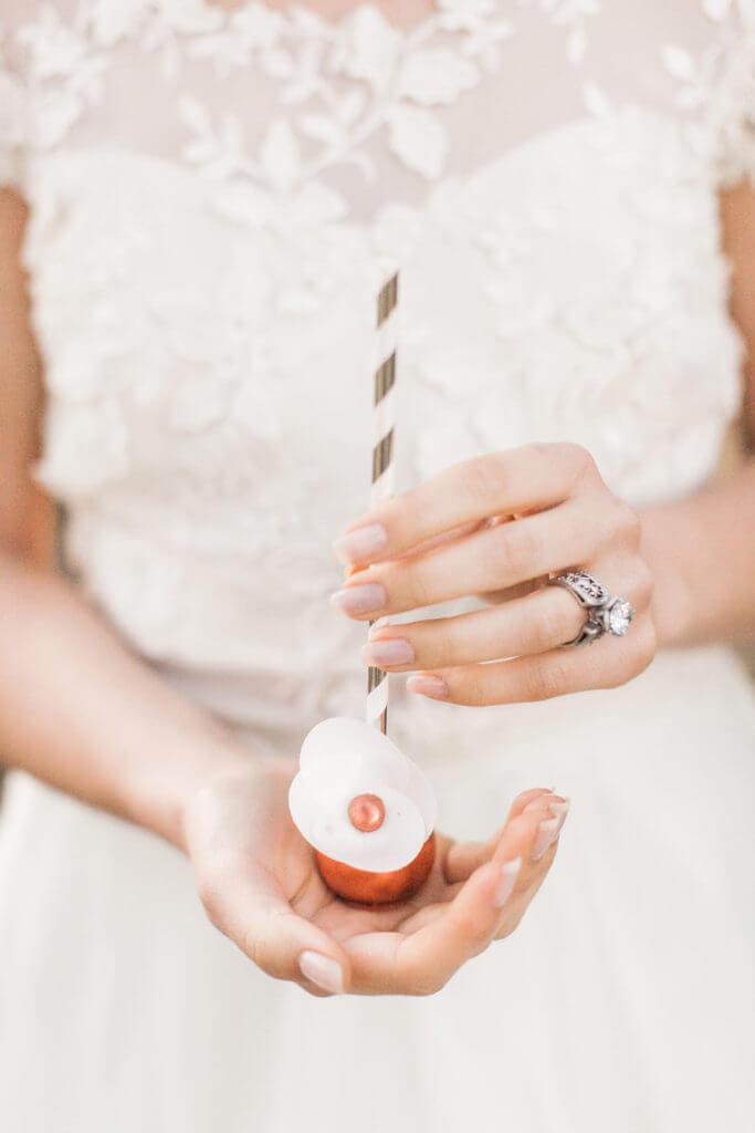 Hands of a bride holding a pop cake