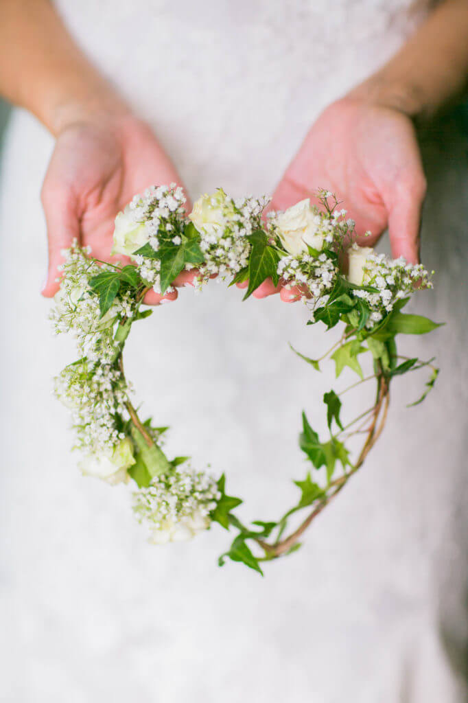 hand holding a tiara made with white roses