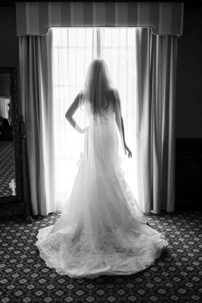 Black and white photos of a bride back with her veil next to a window.