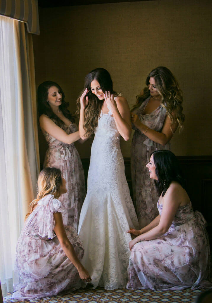 Christina getting in her wedding dress being help by friends