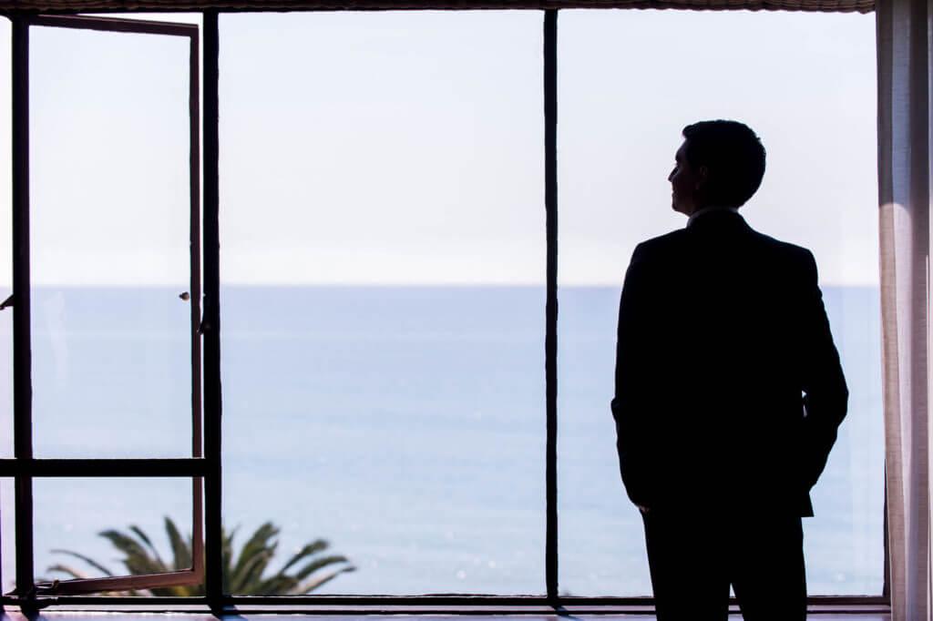 siluette of groom facing the ocean