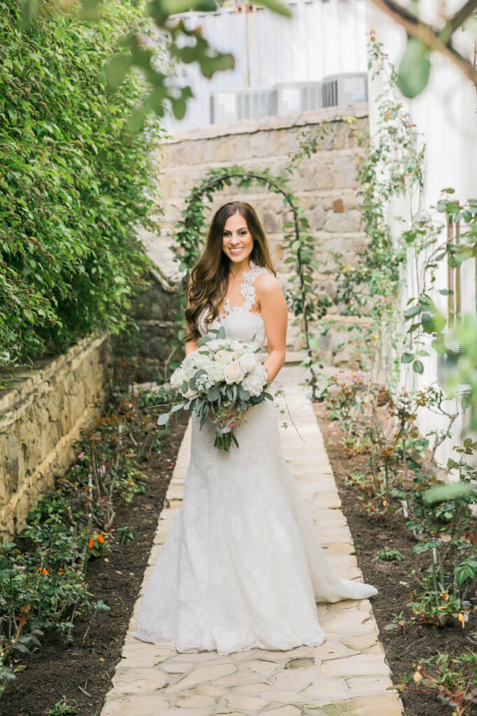Portrait of a bride wearing a long wedding dress with details embellish holding a bouquet of white roses