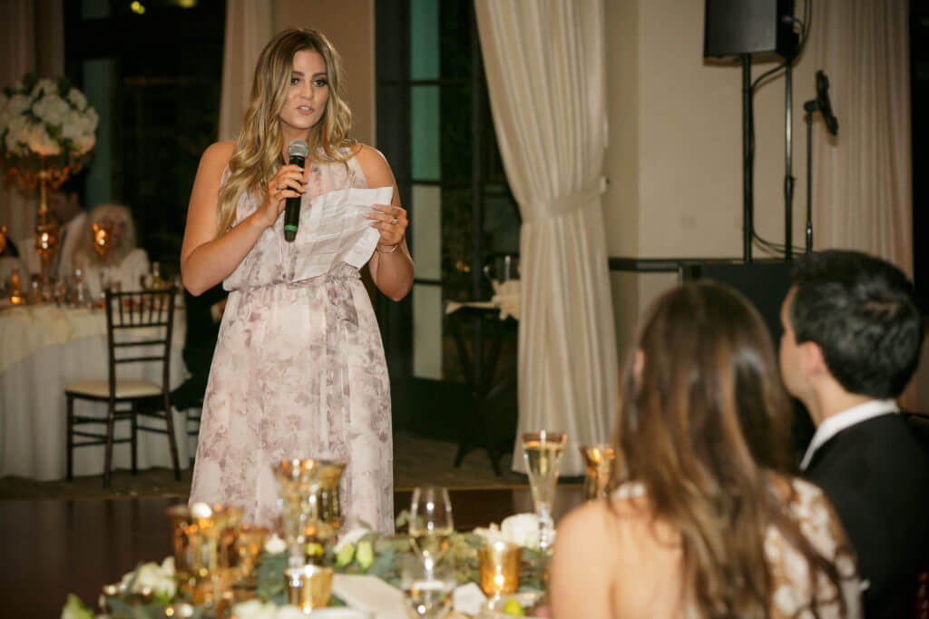 Maid of honor speech during wedding, she is wearing a soft pattern dress with gray and pink.