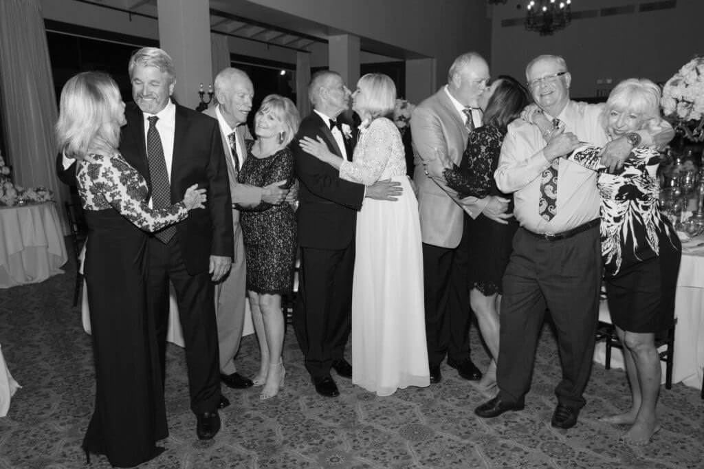 Parents and friends kissing black and white photos reception in a wedding
