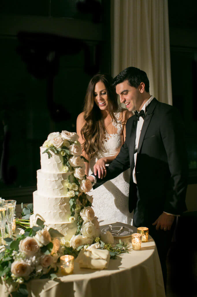 Cake cutting a beautiful 4 tear wedding cake white with soft color roses