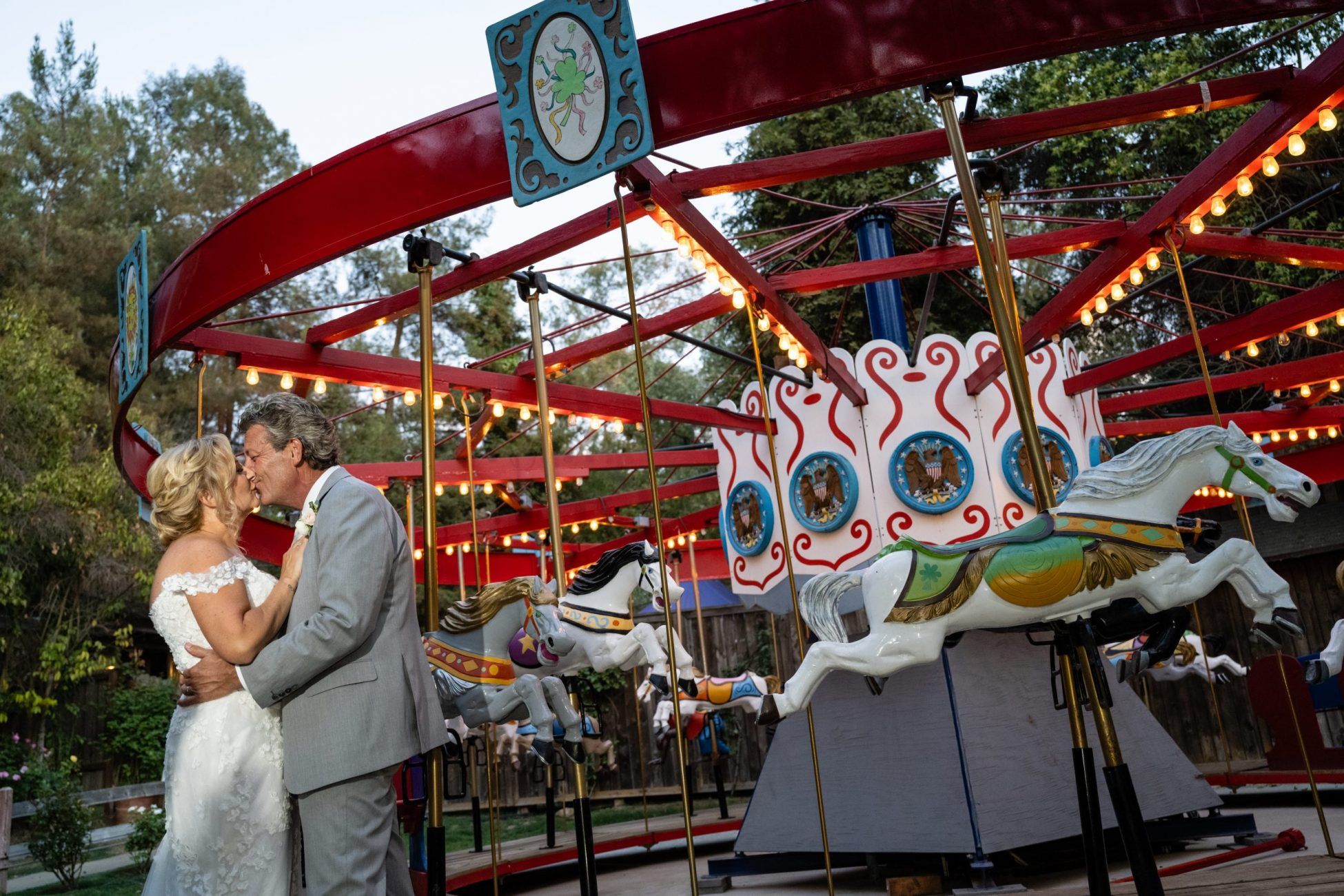 Couple kissing at the carrousel in Calamigos Ranch